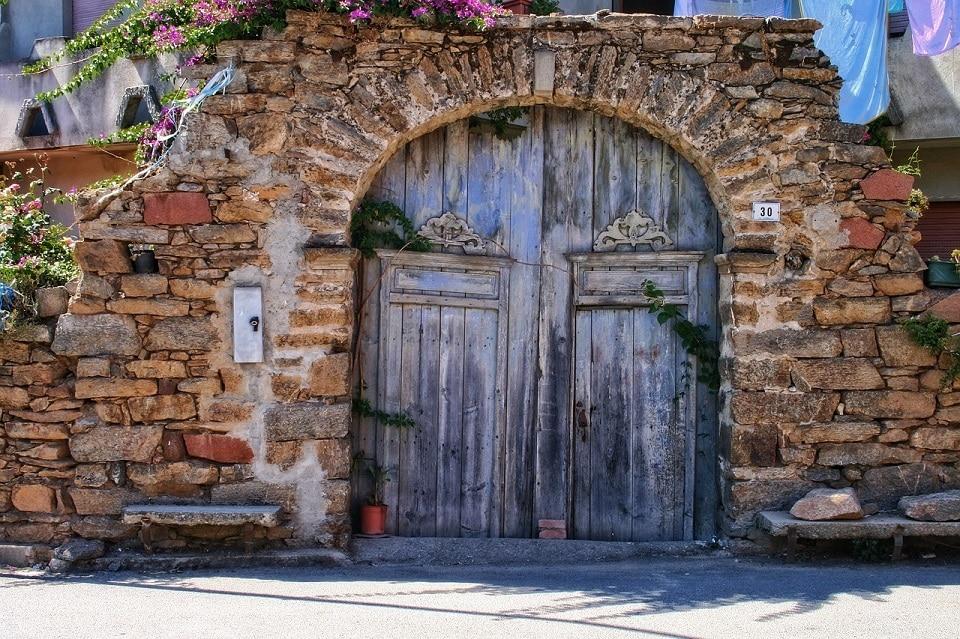Ein typisches Steinhaus in Sardinien mit einer großen Holztür