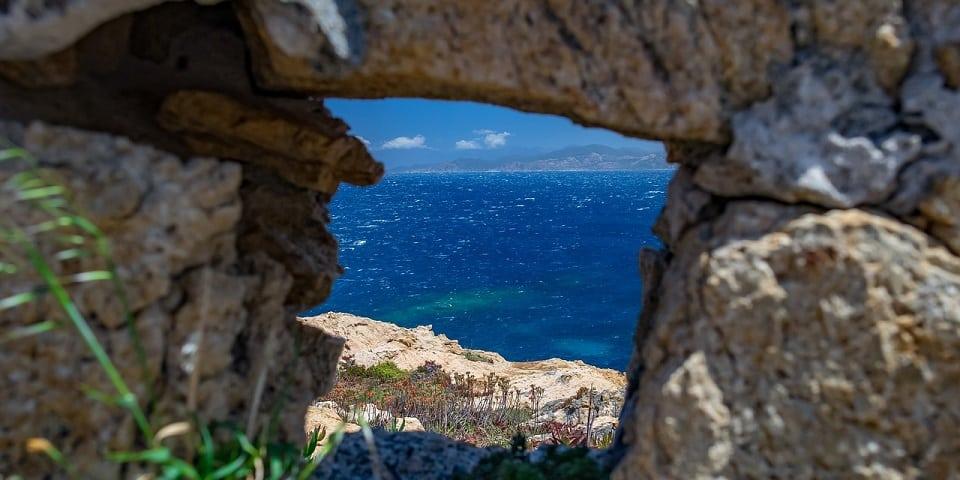 Das blaue Meer von Sardinien von oben zwischen den Rissen eines Steinbogens.